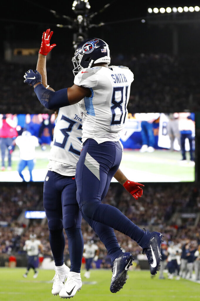 Tennessee Titans tight end Jonnu Smith (81) celebrates his touchdown catch with Tennessee Titans running back Dion Lewis (33) against the Baltimore Ravens during the first half an NFL divisional playoff football game, Saturday, Jan. 11, 2020, in Baltimore. (AP Photo/Julio Cortez)
