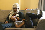 Shukri Olow, left, a Muslim woman who is running for King County Council District 5, watches television with her son, Khalid Ahmed, 9, Friday, Aug. 13, 2021, at their home in Kent, Wash., south of Seattle. Muslim Americans in their 20s and 30s who grew up amid the aftershocks of the Sept. 11, 2001 terrorist attacks came of age in a world not necessarily attuned to their interests, their happiness and their well-being. Olow says the aftermath of the attacks has helped motivate her to become a community organizer and to run for office in Washington state. (AP Photo/Karen Ducey)