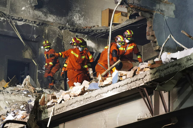 Firefighters look for victims in damaged buildings in the aftermath of a tanker truck explosion near a highway in Wenling in eastern China's Zhejiang province early Sunday, June 14, 2020. More than a dozen were killed and others injured after the tanker truck veered off the Shenyang-Haikou Expressway after the explosion. (Chinatopix via AP)