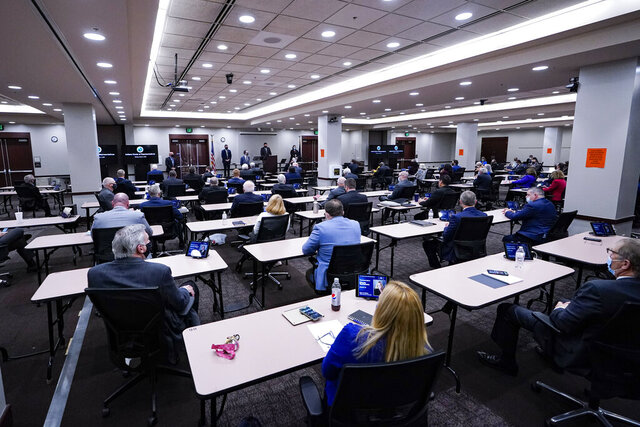 Members of the Indiana House convene in the House chamber in the Indiana Government Center in Indianapolis, Monday, Jan. 4, 2021. The House is meeting in a conference room in the state office building to increase social distancing due to COVID-19. (AP Photo/Michael Conroy)