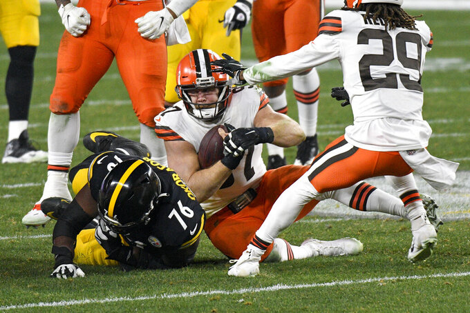 Cleveland Browns defensive end Porter Gustin (97) comes down with an interception with Pittsburgh Steelers offensive tackle Chukwuma Okorafor (76) defending during the first half of an NFL wild-card playoff football game in Pittsburgh, Sunday, Jan. 10, 2021. (AP Photo/Don Wright)