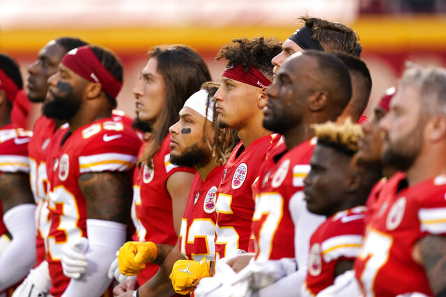 FILE - In this Thursday, Sept. 10, 2020 file photo, Kansas City Chiefs players, including quarterback Patrick Mahomes (15) stand with teammates for a presentation on social justice before an NFL football game against the Houston Texans, in Kansas City, Mo. The NFL's new stance encouraging players to take a stand against racial injustice got its first test as some fans of the Super Bowl champion Kansas City Chiefs booed during a moment of silence to promote the cause, touching off a fresh debate on how players should use their voice. (AP Photo/Charlie Riedel, File)