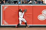 Baltimore Orioles' Dwight Smith Jr. slams into the wall as he pursued a ball that went for a double by New York Yankees' Gio Urshela during the third inning of a baseball game Tuesday, May 21, 2019, in Baltimore. (AP Photo/Nick Wass)