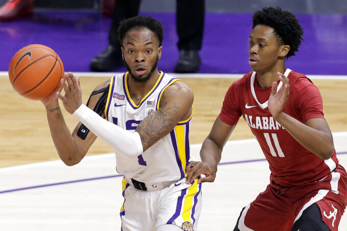 LSU guard Ja'Vonte Smart (1) passes the ball as Alabama guard Joshua Primo (11) defends during the first half of an NCAA college basketball game in Baton Rouge, La., Tuesday, Jan. 19, 2021. (AP Photo/Brett Duke)