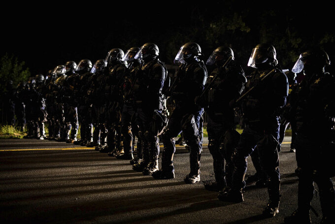 In this Aug. 8, 2020 photo, Portland, Ore., police officers in riot gear stand guard near the Portland police union building. Despite passage of a 2020 Oregon law tracking decertified officers statewide, most complaints of misconduct remain closed. (Maranie Rae Staab via AP)