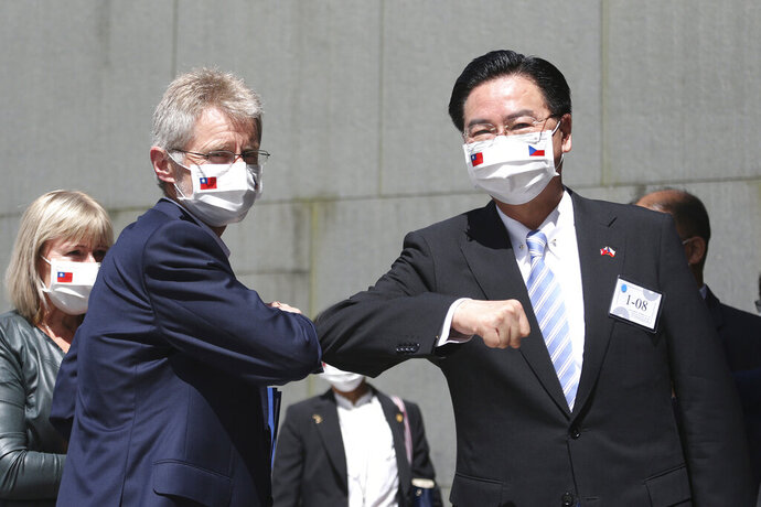 Czech Senate President Milos Vystrcil, front left, is greeted by Taiwanese Foreign Minister Joseph Wu as he arrives for delivering a speech at National Chengchi University in Taipei, Taiwan, Monday, Aug. 31. 2020. Vystrcil arrived in Taiwan on Sunday accompanied by Prague Mayor Zdenek Hrib and more than 80 representatives from government, business and academia for a six-day visit. (AP Photo/Chiang Ying-ying)