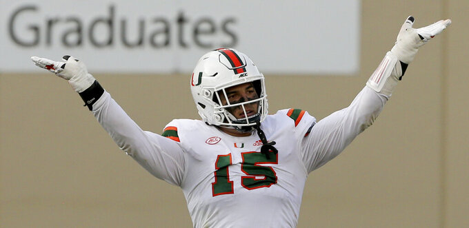 FILE - In this  Saturday, Nov. 14, 2020 file photo, Jaelan Phillips of Miami celebrates a defensive stop during the second half of an NCAA college football game against Virginia Tech in Blacksburg, Va. With Oregon's Penei Sewell likely to be long gone, two other heralded tackles could be available to the Vikings at No. 14: Northwestern's Rashawn Slater and Virginia Tech's Christian Darrisaw. Slater has a random connection to Minnesota: His father, Reggie Slater, played in the NBA for the Timberwolves in parts of two seasons.(Matt Gentry/The Roanoke Times via AP, Pool)