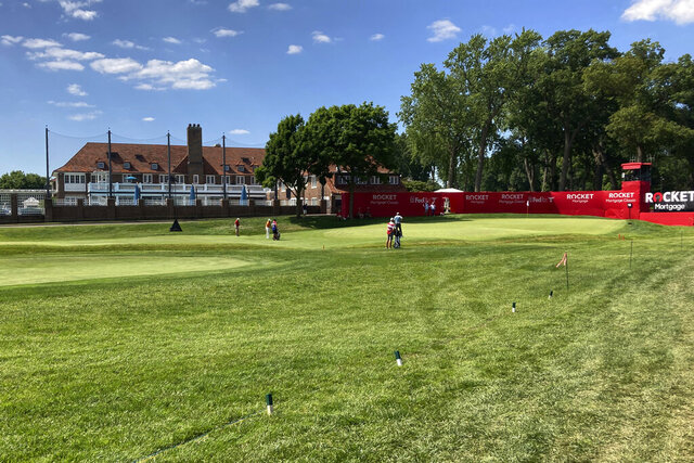 Golfers hit onto the 18th green during the first round of the Rocket Mortgage Classic golf tournament, Thursday, July 2, 2020, at the Detroit Golf Club in Detroit. Flags and markers block off an area where fans would normally be standing. The PGA Tour is hosting its fourth tournament since the world's best golfers resumed competing sans fans. (AP Photo/Larry Lage)