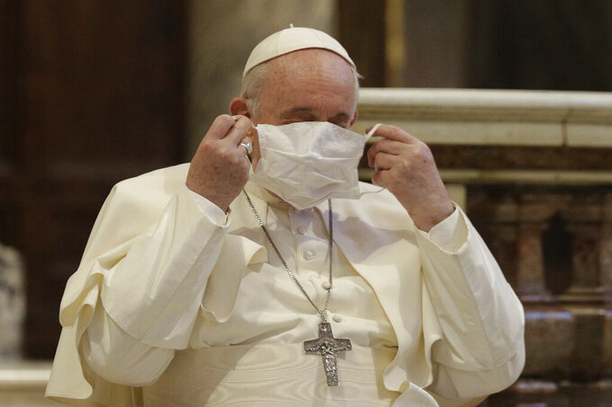 FILE - In this Oct. 20, 2020, file photo, Pope Francis puts on his face mask as he attends an inter-religious ceremony for peace in the Basilica of Santa Maria in Aracoeli, in Rome. Pope Francis has been warned of potential exposure to COVID-19 after a Vatican diplomat was infected, Australian media reported on Friday, Oct. 23, 2020. Archbishop Adolfo Tito Yllana, the Holy See's ambassador to Australia, had a face-to-face meeting with Francis at the Vatican on Oct. 6, less than two weeks before testing positive to COVID-19 in Australia, Nine News reported. (AP Photo/Gregorio Borgia)