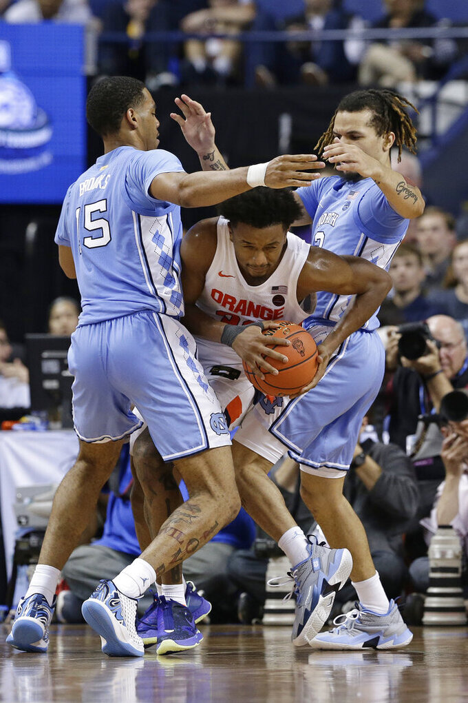 Syracuse forward Elijah Hughes is pressured by North Carolina forward Armando Bacot (5) and guard Cole Anthony (2) during the second half of an NCAA college basketball game at the Atlantic Coast Conference tournament in Greensboro, N.C., Wednesday, March 11, 2020. (AP Photo/Gerry Broome)