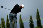 Graeme McDowell hits from the first tee as a rainbow forms on the horizon during second round of the Tournament of Champions golf event, Friday, Jan. 3, 2020, at Kapalua Plantation Course in Kapalua, Hawaii. (AP Photo/Matt York)