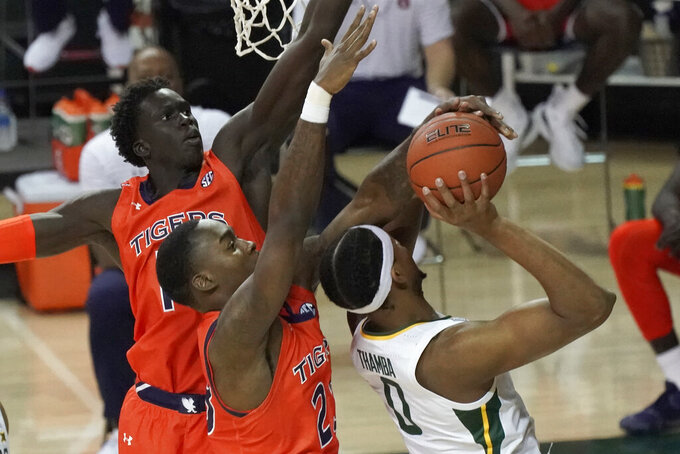 Baylor's Flo Thamba (0) has his shot blocked by Auburn's Jaylin Williams (23) as Auburn's JT Thor closes in during the first half of an NCAA college basketball game in Waco, Texas, Saturday, Jan. 30, 2021. (AP Photo/Chuck Burton)
