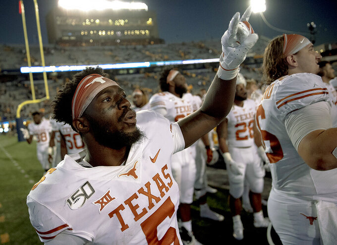 "Texas defensive back D'Shawn Jamison (5) holds up the ""Hook 'Em Horns"" gesture after Texas defeated West Virginia  in an NCAA college football game on Saturday, Oct. 5, 2019, in Morgantown, W. Va. (Nick Wagner/Austin American-Statesman via AP)"