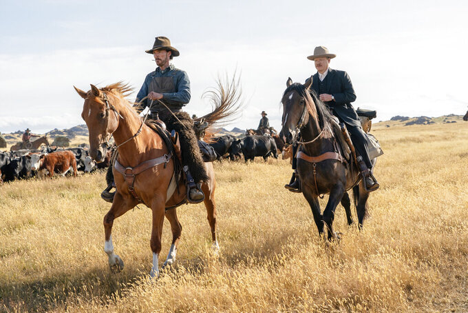 """This image released by Netflix shows Benedict Cumberbatch, left, and Jesse Plemons in a scene from """"The Power of the Dog."""" (Kirsty Griffin/Netflix via AP)"""