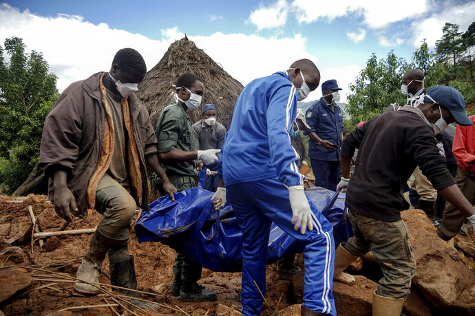 In this photo taken Friday, March 22, 2019, men retrieve the body of 17-year-old Agreement Munanga, who died last Friday after Cyclone Idai caused mudslides in Chimanimani, Zimbabwe. As flood waters began to recede in parts of Mozambique, Zimbabwe and Malawi fears rose that the death toll could soar as bodies are revealed. (AP Photo/KB Mpofu)