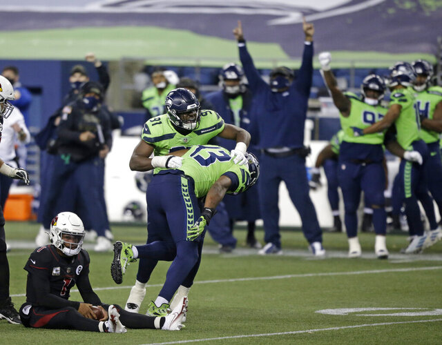 Seattle Seahawks defensive end Carlos Dunlap (43) celebrates with defensive end L.J. Collier (91) after Dunlap sacked Arizona Cardinals quarterback Kyler Murray, left, late in the second half of an NFL football game, Thursday, Nov. 19, 2020, in Seattle. The Seahawks won 28-21. (AP Photo/Lindsey Wasson)