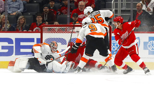 Philadelphia Flyers goaltender Brian Elliott (37) stops a Detroit Red Wings left wing Darren Helm (43) shot in the first period of an NHL hockey game Monday, Feb. 3, 2020, in Detroit. (AP Photo/Paul Sancya)