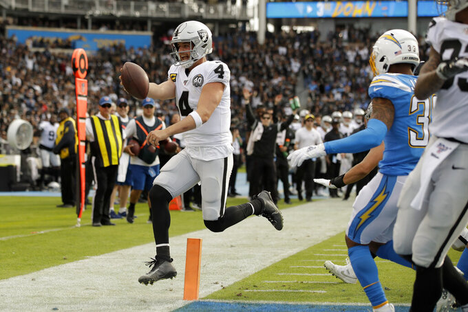 Oakland Raiders quarterback Derek Carr scores against the Los Angeles Chargers during the first half of an NFL football game Sunday, Dec. 22, 2019, in Carson, Calif. (AP Photo/Marcio Jose Sanchez)