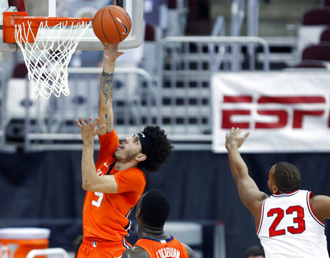 Illinois guard Andre Curbelo, left, goes up to shoot in front of teammate center Kofi Cockburn, center, and Ohio State forward Zed Key during the first half of an NCAA college basketball game in Columbus, Ohio, Saturday, March 6, 2021. (AP Photo/Paul Vernon)