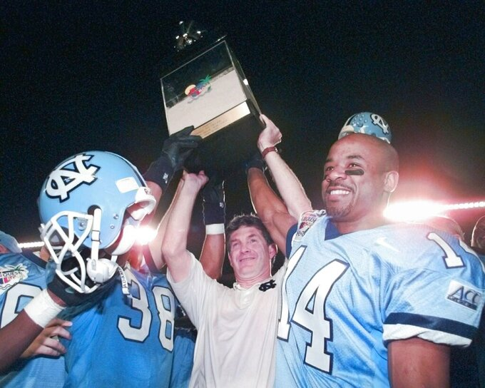 FILE - In this Dec. 30, 1995, file photo, North Carolina NCAA college football coach Mack Brown hoists the Carquest trophy with players Eric Thomas (38) and Marcus Wall (14) after they defeated Arkansas  20-10 in Miami, Fla. Brown is back for his second stint as coach of the Tar Heels. (AP Photo/Hans Deryk, File)