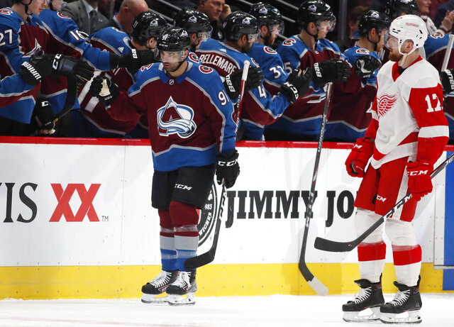 Colorado Avalanche center Nazem Kadri, back, is congratulated as he passes the team box after scoring a goal as Detroit Red Wings defenseman Filip Hronek looks on in the second period of an NHL hockey game Monday, Jan. 20, 2020, in Denver. (AP Photo/David Zalubowski)