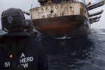 In this July 2021 photo provided by Sea Shepherd, crew members of the Ocean Warrior approach a Chinese-flagged vessel whose Indonesian crew said they had been stuck at sea for years. (Isaac Haslam/Sea Shepherd via AP)