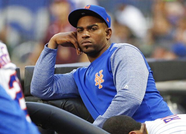 FILE - In this July 24, 2018, file photo, New York Mets' Yoenis Cespedes looks on as his team play the San Diego Padres during the first inning of a baseball game in New York. Cespedes' salary for 2019 was cut in half and his pay for 2020 reduced as part of a settlement of a grievance between the injured outfielder and the Mets. He agreed to a $110 million, four-year contract in December 2016 but has not played since July 20, 2018. The outfielder had surgery to remove bone calcification from his right heel on Aug. 2, 2018, and his left that Oct. 26. (AP Photo/Frank Franklin II, File)