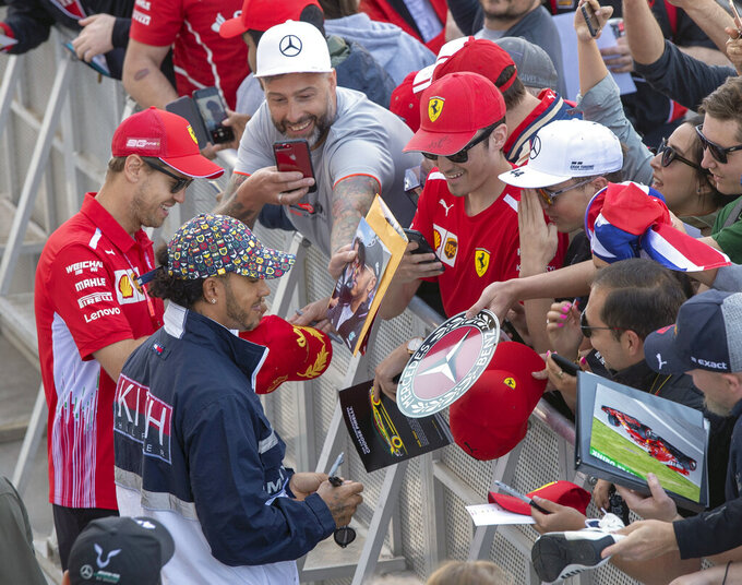 Ferrari driver Sebastian Vettel, far left, of Germany, and Mercedes driver Lewis Hamilton, of Great Britain, sign autographs during the open house day for the Canadian Grand Prix auto race in Montreal, Thursday, June 6, 2019. (Ryan Remiorz/The Canadian Press via AP)