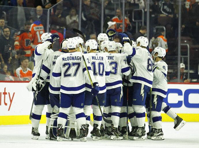 The Tampa Bay Lightning celebrate their overtime win in an NHL hockey game against the Philadelphia Flyers, Saturday, Nov. 17, 2018, in Philadelphia. The Lightning won 6-5. (AP Photo/Tom Mihalek)