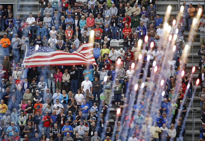 FILE - Fans cheer and wave a flag as fireworks explode during the playing of the national anthem before the start the Xfinity series auto race at Daytona International Speedway, Saturday, Feb. 21, 2015, in Daytona Beach, Fla. NASCAR has built itself around its traveling show, every weekend a super-charged event of concerts, camping and infield carousing that closes with a Cup race. The party has been canceled during the pandemic but the playoffs go on, starting Sunday, Sept. 6, 2020, without any of the pomp and circumstance. (AP Photo/John Raoux, File)