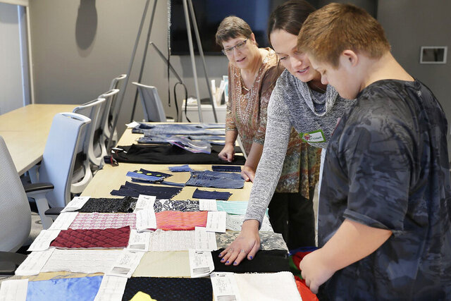 In this Oct. 27, 2019 photo, from left, Janet Littleton of Laurel, Del. watches, University of Delaware senior Elizabeth deBruin shows fabric swatches to Littleton's grandson, 11-year-old Jayden Niblett of Seaford, Del., at the Innovation Health and Design Lab at the University of Delaware in Newark, Del. Niblett was participating in the Down Syndrome Research Party. (Elizabeth Robertson/The Philadelphia Inquirer via AP)