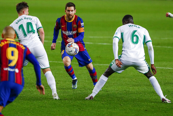 Barcelona's Lionel Messi, center, views for the ball during the Spanish La Liga soccer match between FC Barcelona and Elche at the Camp Nou stadium in Barcelona, Spain, Wednesday, Feb. 24, 2021. (AP Photo/Joan Monfort)