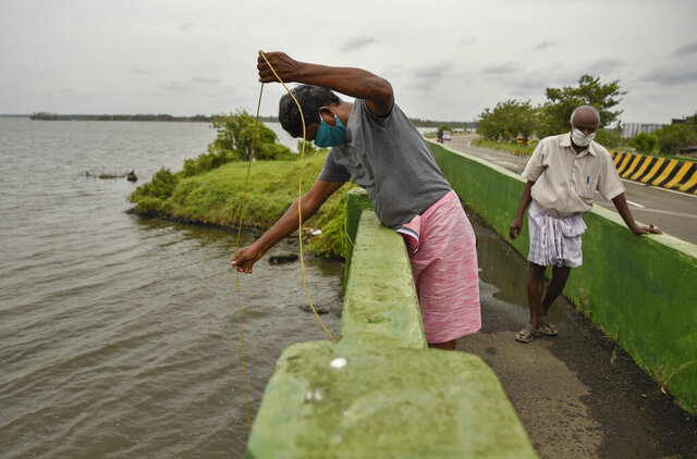 Indians wearing face masks engage in fishing during lockdown to curb the spread of coronavirus in Kochi, Kerala, India, Saturday, May 16, 2020. Prime Minister Narendra Modi's government is due to announce a decision this weekend on whether to extend the 54-day-old lockdown. (AP Photo/R S Iyer)