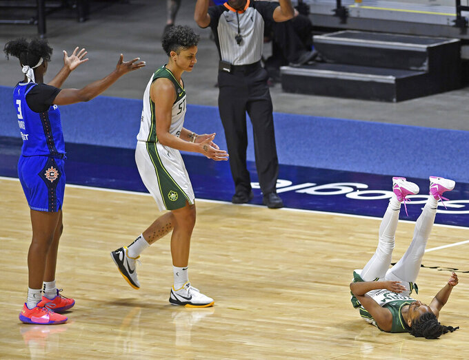 Connecticut Sun guard Kaila Charles, left, questions a call as Seattle Storm forward Candice Dupree, center, moves to help Storm guard Kiana Willams off the floor following a foul in the second half of a WNBA basketball game Sunday, June 13, 2021, at Mohegan Sun Arena in Uncasville, Conn. (Sean D. Elliot/The Day via AP)