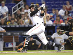 Miami Marlins' Miguel Rojas follows through on a single during the first inning of a baseball game against the Pittsburgh Pirates, Sunday, April 15, 2018, in Miami. (AP Photo/Lynne Sladky)