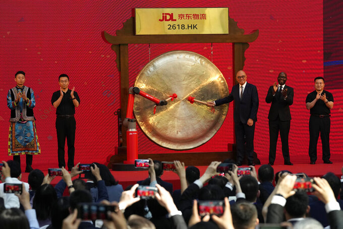 Willie Tan, an executive officer of Skechers Greater China, and customer of JD Logistics sound the gong together with a robot arm at a a ceremony to observe virtually the listing of JD Logistics on the Hong Kong stock exchange from JD.com headquarters in Beijing on Friday, May 28, 2021. JD Logistics' shares jumped 14% in their trading debut Friday in Hong Kong. The company is a subsidiary of Chinese e-commerce giant JD.com. It is the latest technology company to list in the semi-autonomous Chinese city as Beijing intensifies scrutiny of the technology sector. (AP Photo/Ng Han Guan)