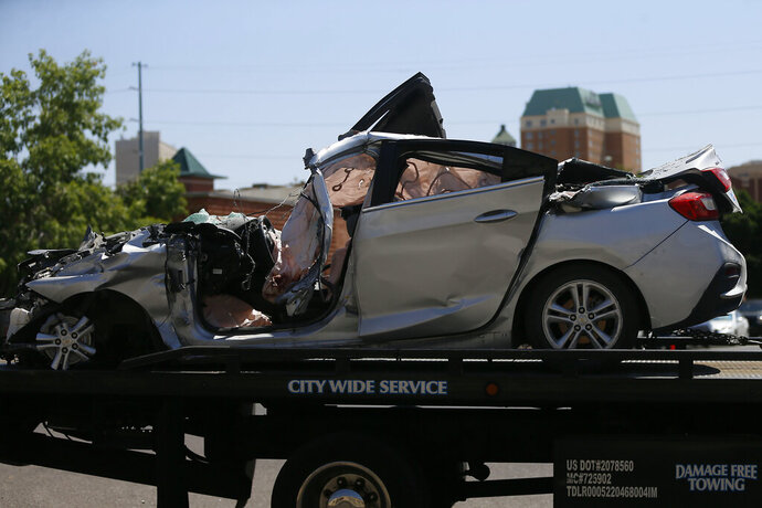 A damaged silver four-door vehicle is transported after being involved in a crash involving 10 people Thursday, June 25, 2020 In El Paso, Texas. Authorities say seven people were killed and three others were injured after a car being pursued by the Border Patrol smashed into a building in a Texas border city. (Briana Sanchez/The El Paso Times via AP)