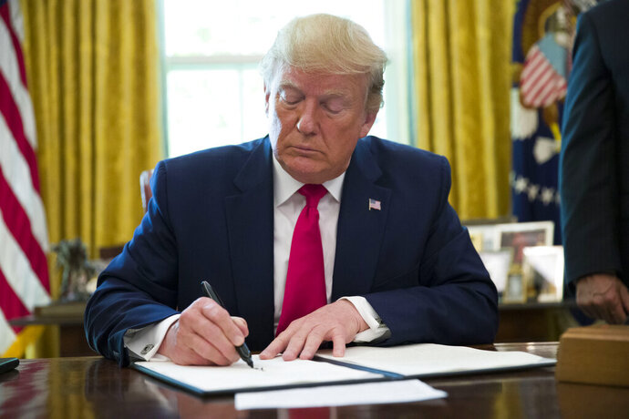 President Donald Trump signs an executive order to increase sanctions on Iran, in the Oval Office of the White House, Monday, June 24, 2019, in Washington. (AP Photo/Alex Brandon)