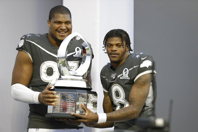 AFC defensive end Calais Campbell, of the Jacksonville Jaguars, (93) and quarterback Lamar Jackson, of the Baltimore Ravens, (8) hold the Pro Bowl trophy after the NFL Pro Bowl football game, Sunday, Jan. 26, 2020, in Orlando, Fla. The AFC defeated the NFC 38-33. Campbell won the MVP defensive player of the game, while Jackson won the MVP offensive player of the game. (AP Photo/Chris O'Meara)