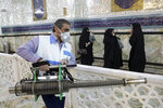 A man disinfects the shrine of the Shiite Saint Imam Abdulazim to help prevent the spread of the new coronavirus in Shahr-e-Ray, south of Tehran, Iran, Saturday, March, 7, 2020. (AP Photo/Ebrahim Noroozi)