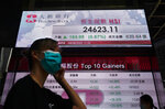 A man wearing a face mask walks past a bank's electronic board showing the Hong Kong share index at Hong Kong Stock Exchange on Tuesday, Aug. 4, 2020. Shares advanced across Asia on Tuesday after Wall Street closed broadly higher on encouraging economic reports, starting off August by closing within 3% of the record high it set in February. (AP Photo/Vincent Yu)