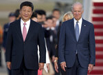 FILE - In this Sept. 24, 2015, file photo Chinese President Xi Jinping and Vice President Joe Biden walk down the red carpet on the tarmac during an arrival ceremony in Andrews Air Force Base, Md. China has fast become a top election issue as President Donald Trump and Democrat Joe Biden engage in a verbal brawl over who's better at playing the tough guy against Beijing. (AP Photo/Carolyn Kaster, File)