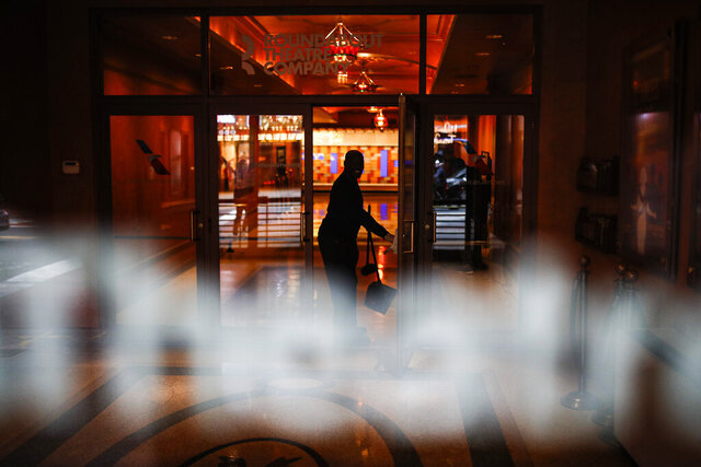 A custodian cleans the lobby of the Roundabout Theatre Company in Times Square, Thursday, March 12, 2020, in New York. New York City Mayor Bill de Blasio said Thursday he will announce new restrictions on gatherings to halt the spread of the new coronavirus in the coming days. For most people, the new coronavirus causes only mild or moderate symptoms. For some it can cause more severe illness. (AP Photo/John Minchillo)