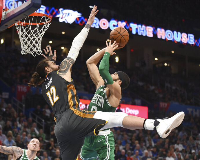Boston Celtics forward Jayson Tatum (0) goes up for a shot over Oklahoma City Thunder center Steven Adams (12) in the second half of an NBA basketball game, Sunday, Feb. 9, 2020, in Oklahoma City. (AP Photo/Kyle Phillips)