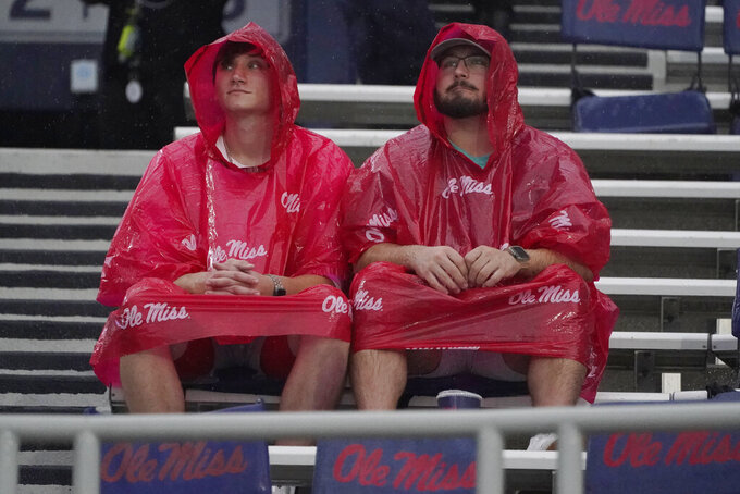 Mississippi fans sit in the rain prior to an NCAA college football game against Tulane, Saturday, Sept. 18, 2021, in Oxford, Miss. A weather delay was called by officials. (AP Photo/Rogelio V. Solis)