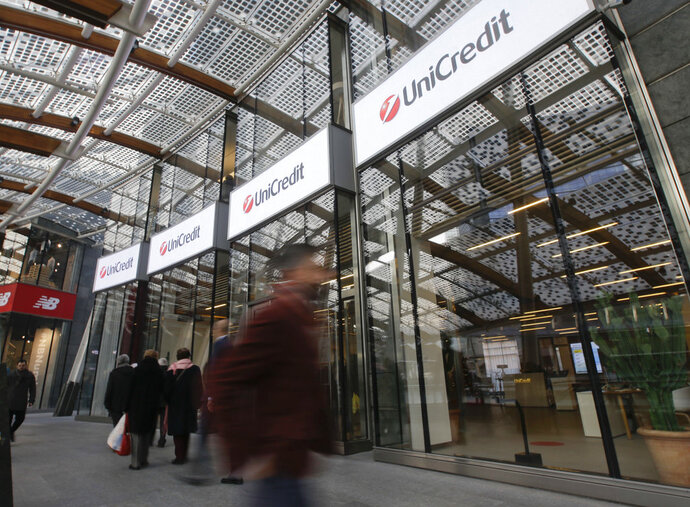 FILE - In this file photo dated Tuesday, Dec. 13, 2016, the entrance of the UniCredit tower at the Porta Nuova business district in Milan, Italy.  Italian bank UniCredit said Thursday Nov. 8, 2018, that one-off provisions to cover any settlement for alleged U.S. sanctions violations in Iran and a write-down on its Turkish unit dropped third-quarter profits by 99 percent. (AP Photo/Luca Bruno, FILE)