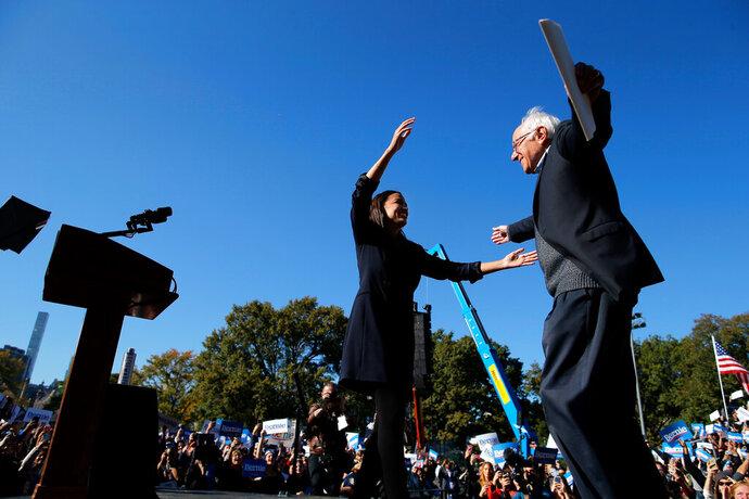 Democratic presidential candidate Sen. Bernie Sanders, I-Vt., hugs Rep. Alexandria Ocasio-Cortez, D-N.Y. during a campaign rally on Saturday, Oct. 19, 2019 in New York. (AP Photo/Eduardo Munoz Alvarez)
