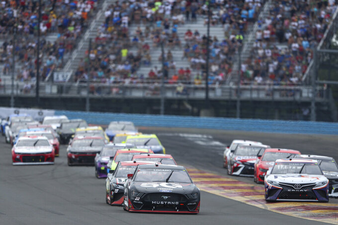 Joey Logano, center, leads a group as they round Turn 1 during a NASCAR Cup Series auto race in Watkins Glen, N.Y., on Sunday, Aug. 8, 2021. (AP Photo/Joshua Bessex)