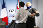 Britain's Prime Minister Boris Johnson, right, greets French President Emmanuel Macron ahead of a bilateral meeting during the G7 summit in Cornwall, England, Saturday June 12, 2021. (Stefan Rousseau/Pool via AP)
