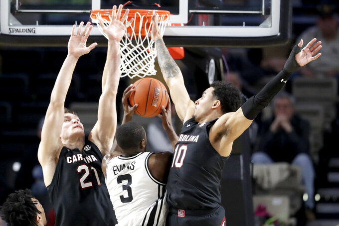 Vanderbilt's Maxwell Evans (3) drives between South Carolina's Maik Kotsar (21) and Justin Minaya (10) in the first half of an NCAA college basketball game Saturday, March 7, 2020, in Nashville, Tenn. (AP Photo/Mark Humphrey)